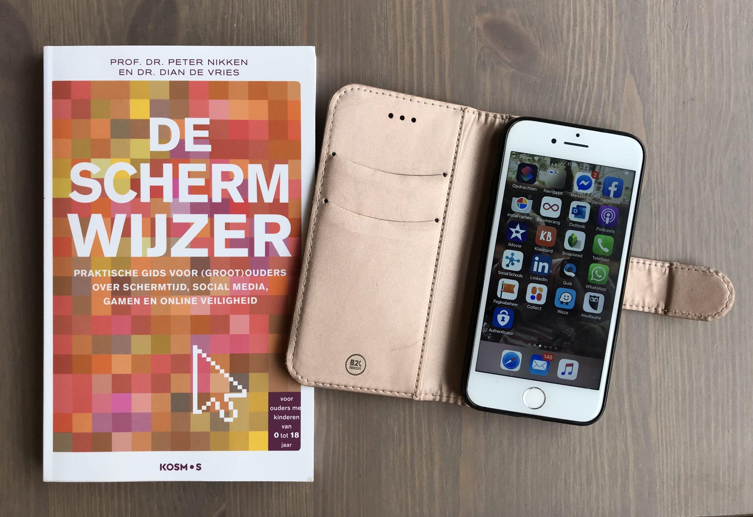 Boekomslag de Scherwijzer plus opengeslagen cover met mobiel